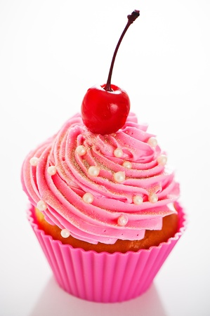 A cupcake in a pink baking cups with pink cream, white decoration and a cherry on the top on white background as a studio shoot Stock Photo