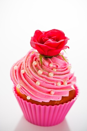 A cupcake in a pink baking cups with pink cream, white decoration and a flower on the top on white background as a studio shoot