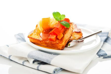 Two slices of french toast with papaya, vanilla ice cream, caramel sauce and mint leaf on a white background as a studio shoot photo