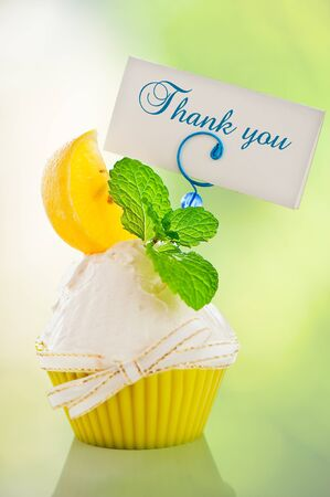 A refreshing lemon cupcake with a leaf of mint and a label for your text on green background as a studio shot photo