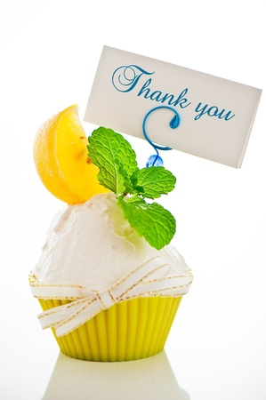 A refreshing lemon cupcake with a leaf of mint and a label for your text on white background as a studio shot photo