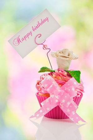 A beautiful pink happy birthday cupcake with flower and a label for your text as studio shot