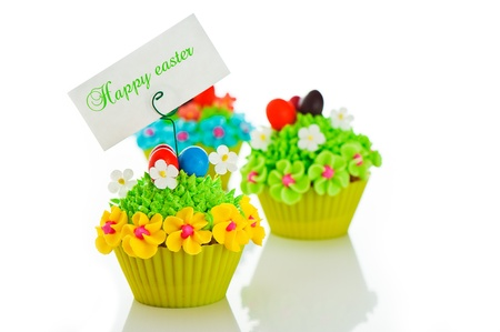 cake pick: Happy easter cupcake with chocolate egg and cream grass as a meadow with flowers on white background