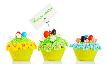 Happy easter cupcake with chocolate egg and cream grass as a meadow with flowers on white background photo