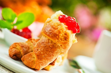 Outdoor breakfast with fresh croissant coffee, jam and flowers as background photo