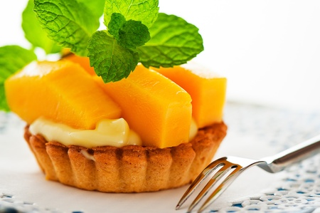 mango fruit: French tart with mango and vanilla pudding on white background as a studio shot Stock Photo