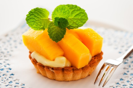 French tart with mango and vanilla pudding on white background as a studio shot photo