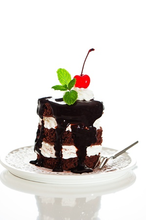 christmas cake: A small chocolate cake with 2 layer white cream, cherry and mint  on top on a white background as a studio shot Stock Photo