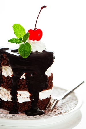 A small chocolate cake with 2 layer white cream, cherry and mint  on top on a white background as a studio shot photo