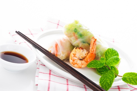 Vegetarian spring roll with carrot, soy sprouts and shrimp on white background as a studio shot photo
