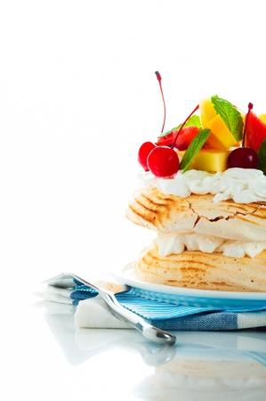 Pavlova met vers fruit mango, ananas, watermeloen, kersen klaar om te dienen op een witte achtergrond als een studio-opname Stockfoto