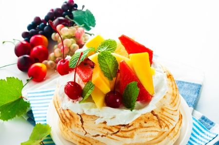 Pavlova with fresh fruit  mango, pineapple, watermelon, cherry  ready  to serve, on white background as a studio shot photo