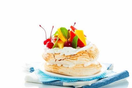 Pavlova with fresh fruit  mango, pineapple, watermelon, cherry  ready  to serve, on white background as a studio shot photo