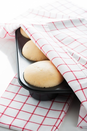 Yeast dough in a muffin pan with a white and red towel on white background as a studio shot