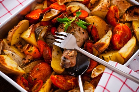 Chicken with vegetables on a baking tray as a studio shot Stock Photo - 12958856