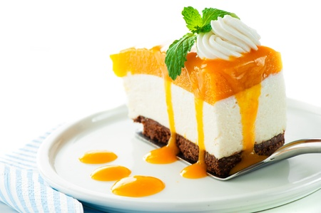 A piece of mango cheese cake on white background as a studio shot