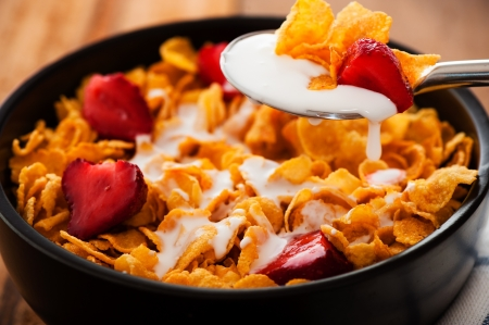 flake: Cereal with milk and strawberries as outdoor shot