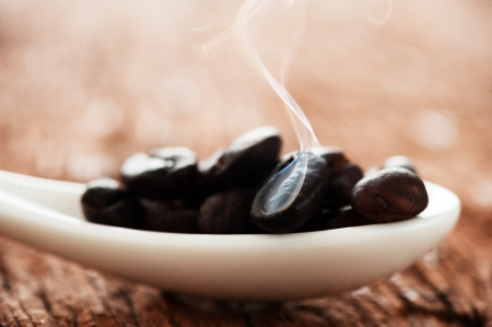 Freshly roasted coffee beans in a white spoon on a wooden  table photo