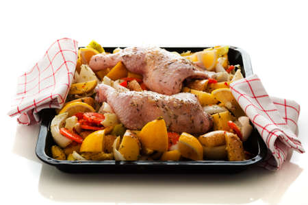 Raw marinated chicken thighs with vegetables on a baking tray photo