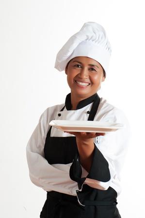 Lachende Aziatische vrouw als chef-kok met een bord in de hand
