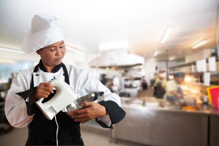 A asian woman as restaurant chef mixing something with a mixer in a bowl. Professional kitchen as background photo