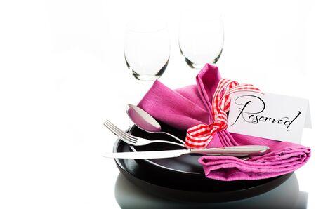 Servies met roze servet en reservatie kaart op witte achtergrond als een studio-opname