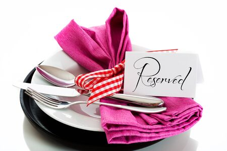 Dinner set with pink napkin and reservation card on white background as a studio shot photo