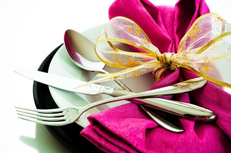 Dinner set with pink napkin on white background as a studio shot