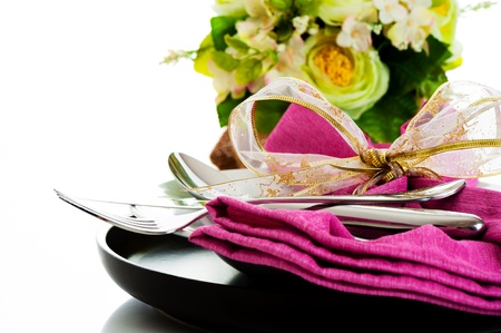 Dinner set with pink napkin and flower on white background as a studio shot photo