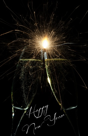 New Year firework celebration with rockets exploding high in the night sky and Happy New Year text below Stock Photo