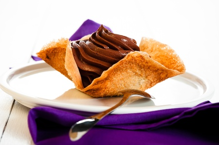 Mousse au chocolat in a tuile basket on white wooden table