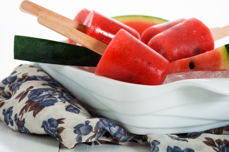 watermelon ice pop in a white bowl with ice and fresch watermelon photo