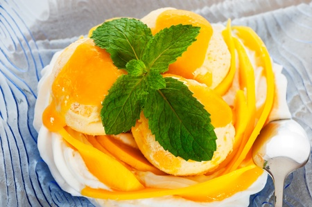 Mango ice cream with fresh mango and whipping cream in a blue glass plate photo