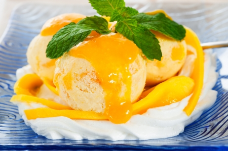 Mango ice cream with fresh mango and whipping cream in a blue glass plate