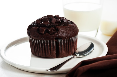 chocolate muffins with chocolate chips on the top on white plate photo
