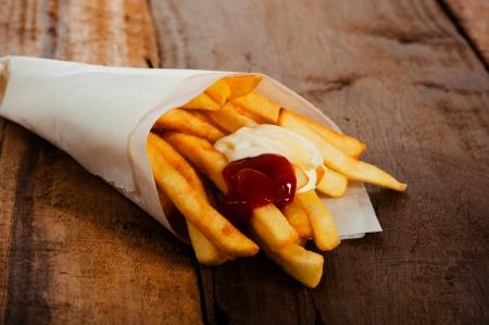 Aardappelen friet in een kleine witte papieren zak met ketchup en mayonnais op hout boord Stockfoto