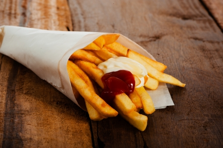 Potatoes fries in a little white paper bag with ketchup and mayonnais on wood board