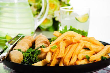 Kartoffeln Pommes mit Frikadellen und Tomaten-Salat auf einem schwarzen Teller. Fresch Zitronengetränk im Hintergrund
