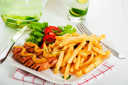 Potatoes fries with sausage mustard and tomato salad. Fresh lemon drink in background photo