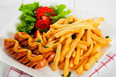 Patatas fritas con salchicha mostaza y ensalada de tomate