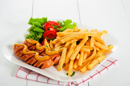Potatoes fries with sausage mustard and tomato salad photo