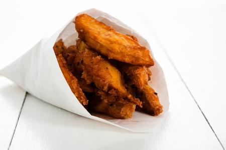 Fried sweet potatoes in a paper bag on white wooden table photo