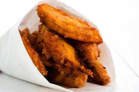 Fried sweet potatoes in a paper bag on white wooden table