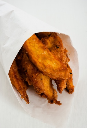 pome: Fried sweet potatoes in a paper bag on white wooden table
