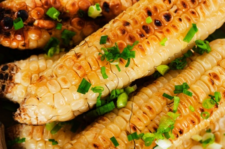 Barbecued corn cobs with herbs on a white plate and a wooden table Stock Photo
