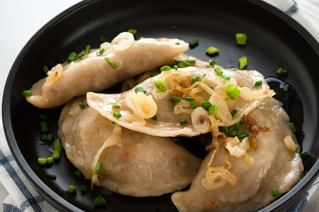 Homemade pierogi or dumpling on black plate photo