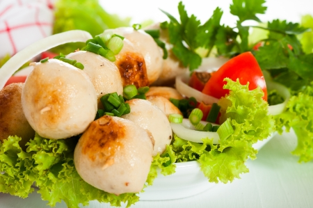 Asian pork or chicken fried meatballs with salad tomatoes and onion on white plate and white background. photo