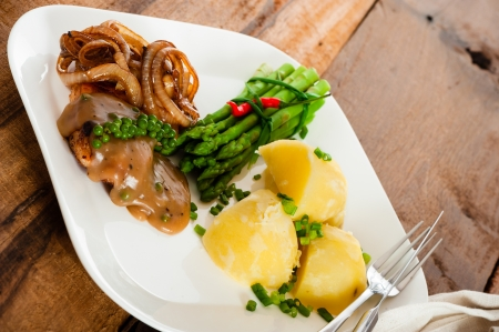 Freshly prepared piece of meat with onions and pepper sauce, cooked potatoes green asparagus and green pepper as a decoration on a white plate. photo