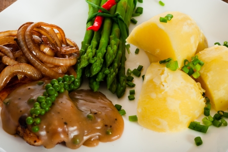Freshly prepared piece of meat with onions and pepper sauce, cooked potatoes green asparagus and green pepper as a decoration on a white plate