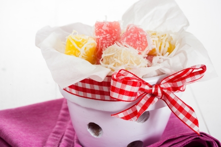 Close up of white yellow and pink coconut ice confectionery with fresh coconuts isolated on white photo